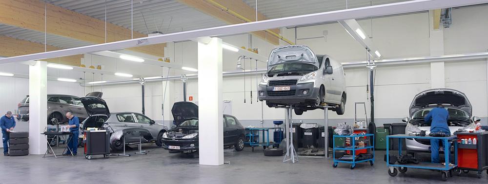 <p>Werkzones voor personenwagens met Autop tweelinghefbruggen.<br />Tegen de wand een Fischer rail-uitlaatgasafzuiging. <br />De friesstructuren met verlichting, hangende energieconnecties, kolommen met verdeling van oliën en diverse vloeistoffen, zijn een ontwerp en constructie van de Workshop Design afdeling.</p>