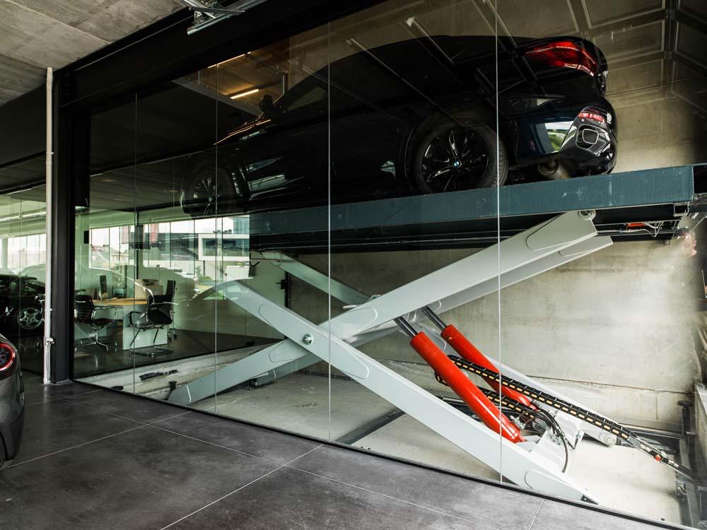 <p><strong>Omer</strong><br />De schaarlift werd in een glazen kooi geplaatst en wordt als marketingmiddel gebruikt.<br />Het voertuig daalt en verschijnt beetje bij beetje voor de klant.</p>